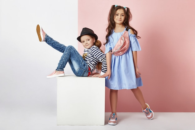 Mode jongen en meisje in stijlvolle kleding op gekleurde muur b
