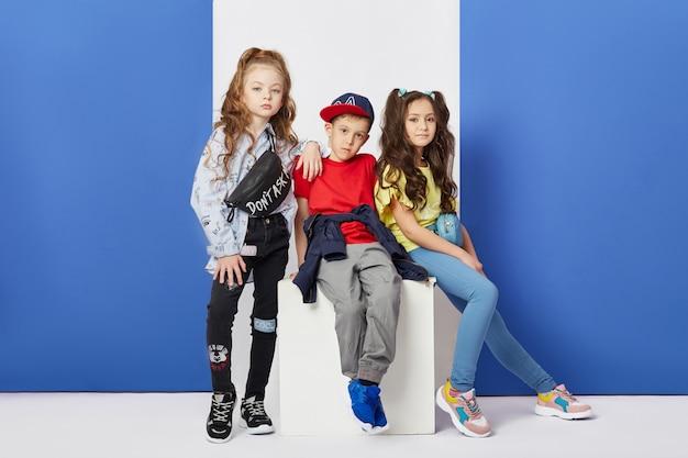 Mode jongen en meisje stijlvolle kleding gekleurde muur