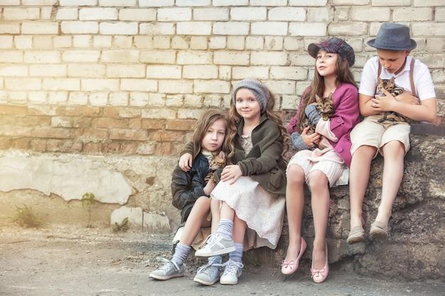 Mode kinderen meisjes en jongens zijn mooi en blij met kleine schattige bengaalse kittens samen