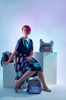 Mode kinderen poseren met een verzameling tassen en clutches. heldere meisjeskleren, blauwe achtergrond