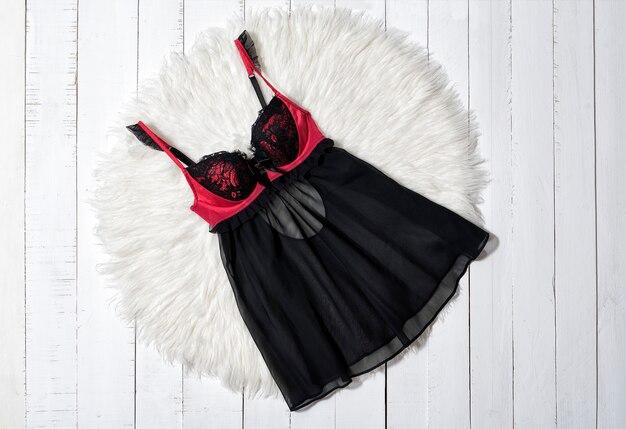 Mode kleding. zwart met rood peignoir op witte houten vloerplanken