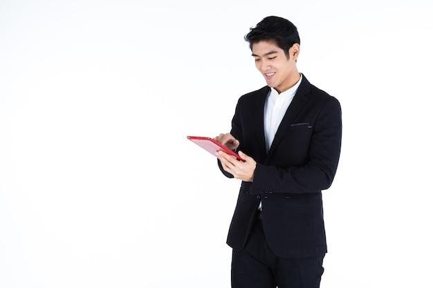 Mode knappe jonge aziatische zakenman met behulp van een tablet typen bericht man geïsoleerd op wit grijs lege kopie ruimte studio achtergrond, indoor studio shoot