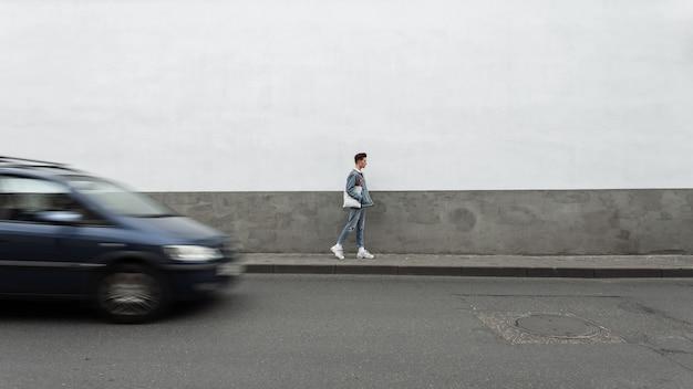 Mode knappe jongeman met vintage stoffen tas in casual modieuze spijkerbroek kleding in witte sneakers reizen op straat in de buurt van weg met bewegingstransport. stijlvolle man geniet van een wandeling door de stad.