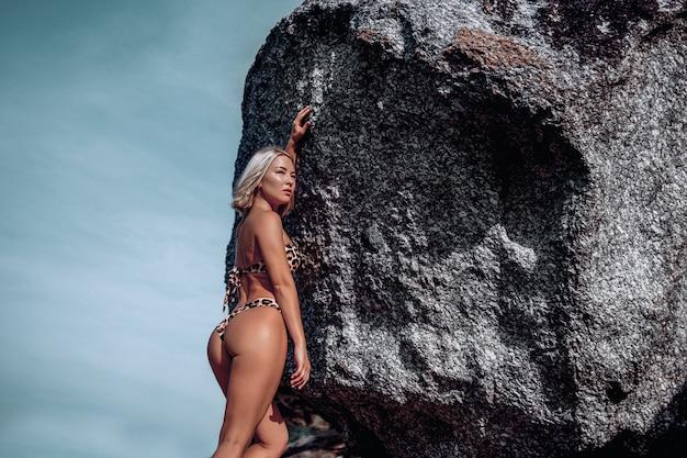 Mode kunst foto van dame in bikini met luipaard print staande in de buurt van rotsen