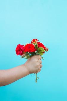 Mode kunst hand van een klein kind met roos boeket