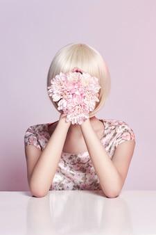 Mode kunst portret vrouw in zomerjurk en bloemen in haar hand