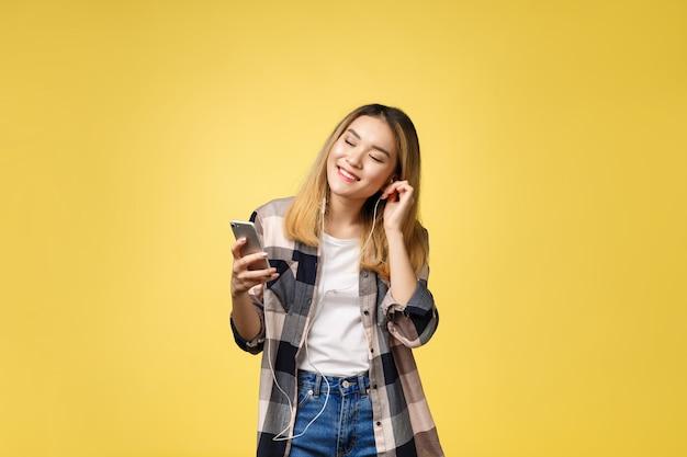 Mode lachende aziatische vrouw luisteren naar muziek in oortelefoons