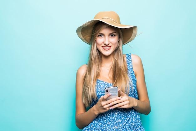 Mode lachende vrouw gebruikt smartphone met strooien hoed op blauwe achtergrond