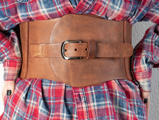 Mode. leren brede damesriem van bruine kleur met een gesp, gekleed voor een meisje in een rood shirt in een kooi