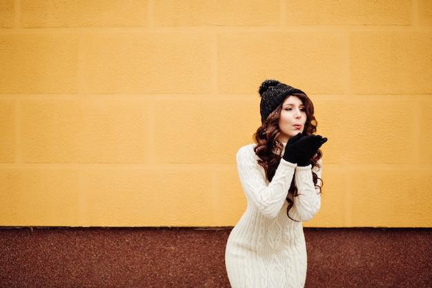 Mode levensstijl portret van een vrij grappige vrouw, zwarte hipster hoed, natuurlijke make-up, witte gebreide trui. stuur een kus, gekke belachelijke liefde.
