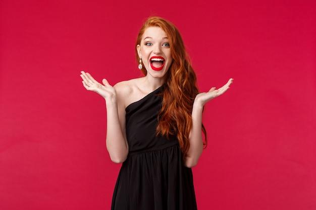 Mode, luxe en beauty concept. wat een leuke verrassing. geamuseerd en blij, opgewonden roodharige vrouw in elegante zwarte jurk, applaus als geweldige prestaties bijwonen, rode muur staan
