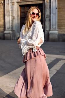 Mode luxe zonnige portret van blonde vrouw die zich voordeed op straat, het dragen van lange zijden rok en blouse