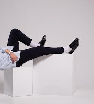 Mode man benen skinny korte broek sokken en schoenen op witte blokjes