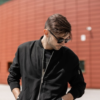Mode man met kapsel in zwarte kleding buitenshuis