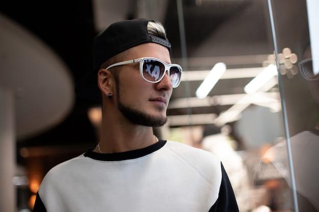 Mode man met zonnebril in stijlvolle uitloper binnenshuis