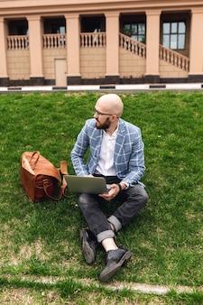 Mode man zittend op het gazon en werken met een laptop freelancer blogger het leven van een modern persoon