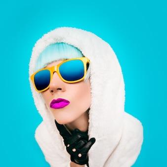 Mode meisje in een witte hoodie op een blauwe achtergrond winter style