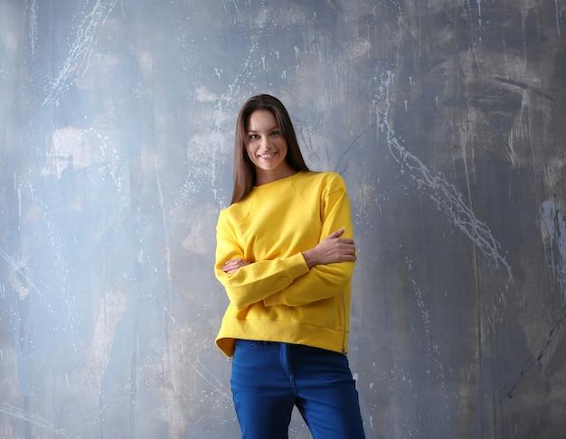 Mode meisje in gele trui op grijze muur achtergrond
