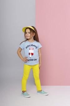 Mode meisje in stijlvolle kleding op gekleurde muur achtergrond. herfst lichte kleding voor kinderen, kind poseren op een gekleurde roze achtergrond