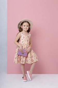 Mode meisje in stijlvolle kleding op gekleurde muur achtergrond. herfst lichte kleding voor kinderen