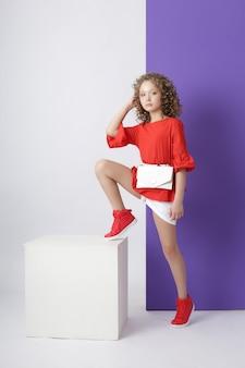 Mode meisje in stijlvolle kleding op gekleurde muur. herfst lichte kleding op kinderen, een kind die zich voordeed op een gekleurde paarse roze achtergrond. ,