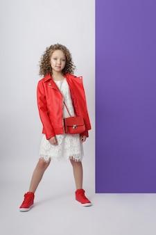 Mode meisje in stijlvolle kleding op gekleurde muur. herfst lichte kleding voor kinderen, een kind dat zich voordeed