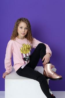 Mode meisje in stijlvolle kleding op gekleurde muur. herfst lichte kleding voor kinderen