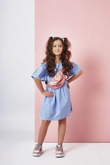 Mode meisje in stijlvolle kleding op gekleurde muur. herfst lichte kleren op kinderen, een kind poseren op een gekleurde paars roze muur