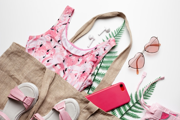 Mode meisje kleding en accessoires op witte achtergrond met groene bladeren zomer strand concept fla...