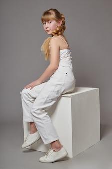 Mode meisje met lang haar in casual kleding zittend op een witte kubus en poseren