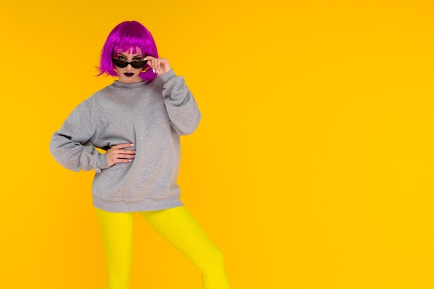 Mode meisje portret op geel. gekke stijl jonge vrouw in roze pruik