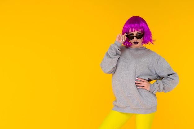 Mode meisje portret op gele achtergrond. gekke stijl jonge vrouw in roze pruik - afbeelding
