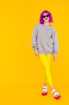 Mode meisje portret op gele achtergrond. gekke stijl jonge vrouw in roze pruik
