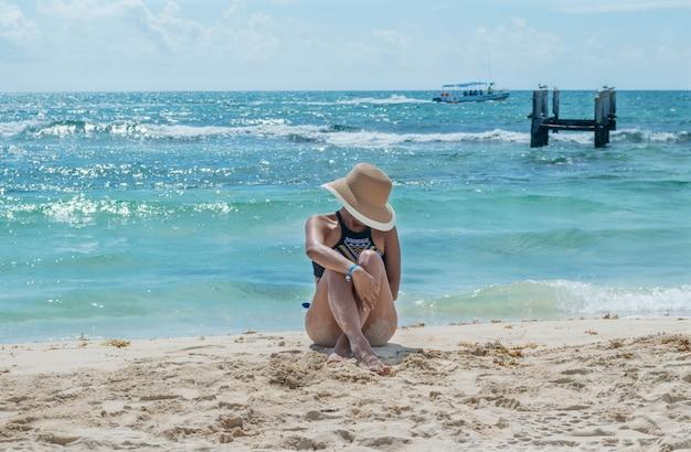 Mode meisje, zittend aan de kust op een mooie middag, met de zee achter, vooraanzicht. vrouw die met gekruiste benen op het zand zit. vrouw met zonnehoed. vrouw looien in de maya riviera