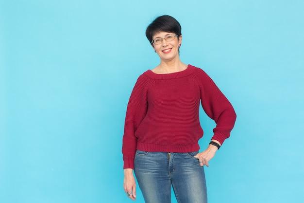 Mode, mensen en stijlconcept - mooie vrouw van middelbare leeftijd in rode sweater en glazen op blauwe muur met exemplaarruimte