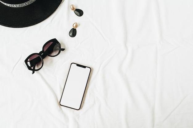 Mode mockup-compositie met elegante damesaccessoires op wit linnen. hoed, zonnebril, oorbellen, smartphone