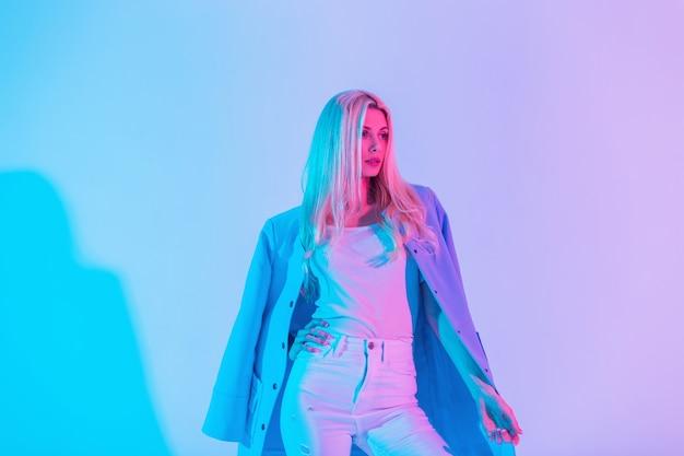 Mode mooi glamoureus zakenmeisje in een stijlvol pak met een blauwe blazer en witte jeans en t-shirt in de studio met neonroze pastelkleuren. creatief gekleurd vrouwelijk portret