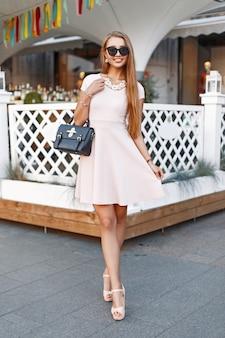 Mode mooi meisje in een roze jurk met een tas in de buurt van het restaurant