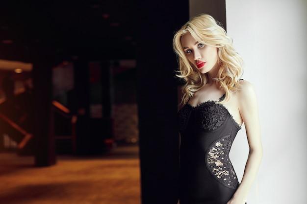 Mode mooie blondevrouw in strakke zwarte kleding die zich dichtbij het venster bevinden.