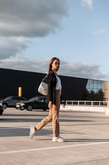 Mode mooie jonge vrouw in vintage casual zakelijke kleding met stijlvolle tas in koele zonnebril wandelingen op de parkeerplaats van de stad op zonnige zomerdag. aantrekkelijk meisje in elegante outfit buiten in de stad.