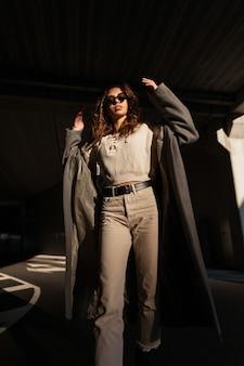 Mode mooie model vrouw met krullend haar in stijlvolle lange jas, trui en broek loopt in de straat in zonlicht. stedelijke casual vrouwelijke stijl