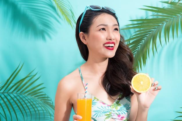 Mode mooie vrouw drinkt sap uit glas over kleurrijke blauwe achtergrond
