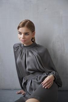 Mode mooie vrouw in een jurk zittend op de vloer tegen de muur. perfecte make-up, romantisch portret