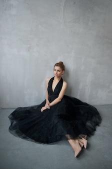 Mode mooie vrouw in een jurk zittend op de vloer