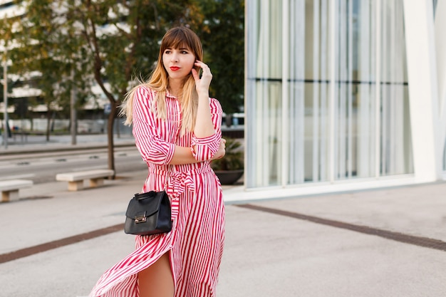 Mode mooie vrouw in rode jurk poseren op straat.