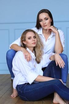 Mode mooie vrouw in wit overhemd en spijkerbroek samen poseren
