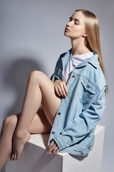 Mode naakte blonde meisje zit op een witte kubus in de studio. mode die de vrouw stelt