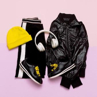 Mode-outfit voor dames stijlvolle zwarte kleding en heldere accessoires sports urban minimal headphone