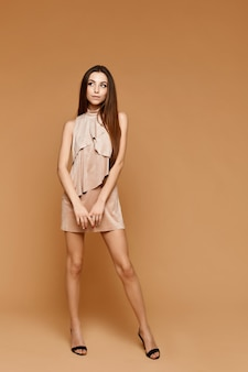 Mode over de volledige lengte van een jonge modelvrouw met perfect slank lichaam en lange benen in een korte beige jurk op het beige oppervlak