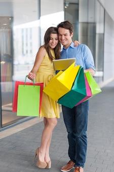 Mode paar met behulp van digitale tablet tijdens het winkelen